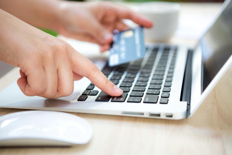 Pessoa com cartão de credito e computador