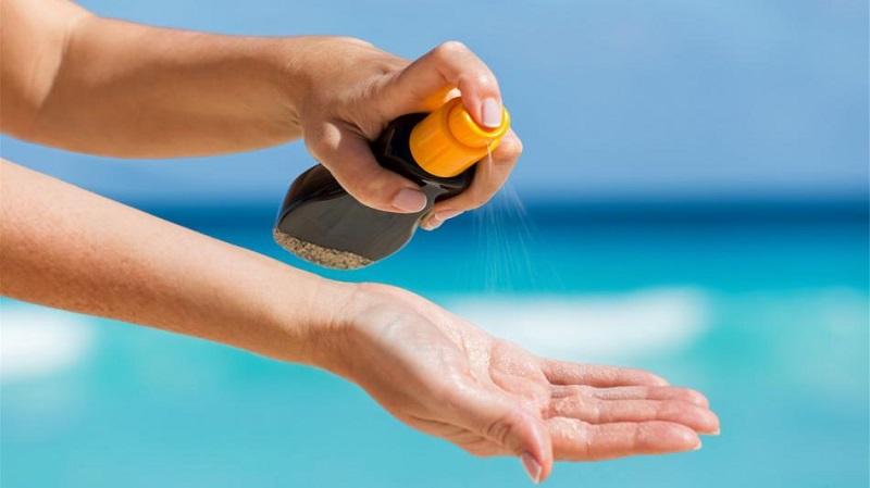 Pessoa passando protetor solar em praia
